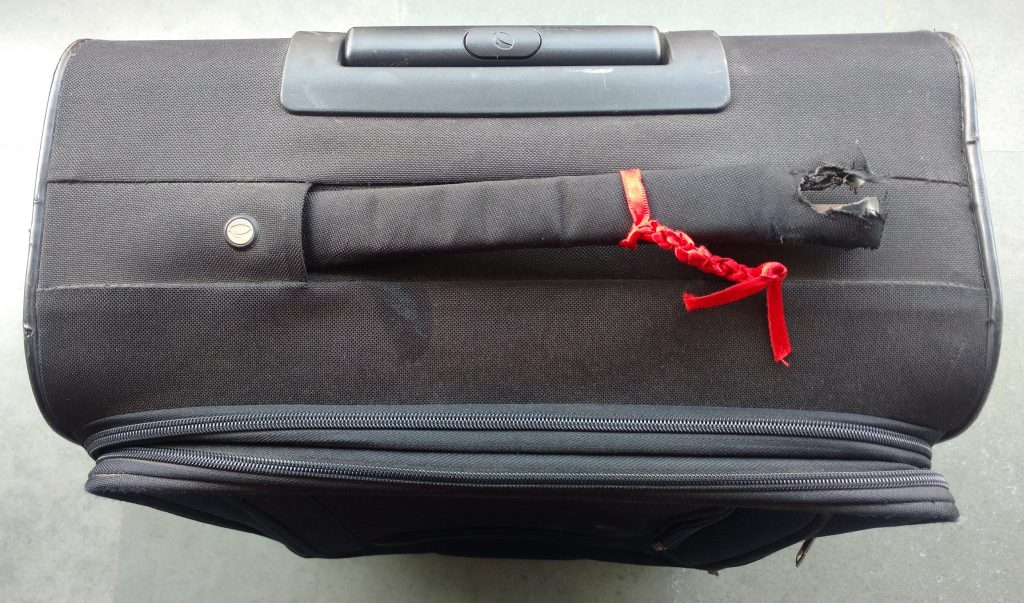 red ribbon and broken handle of suitcase